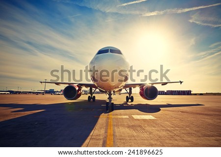 Airplane is taxiing to take off at the sunrise - retro colors - stock photo