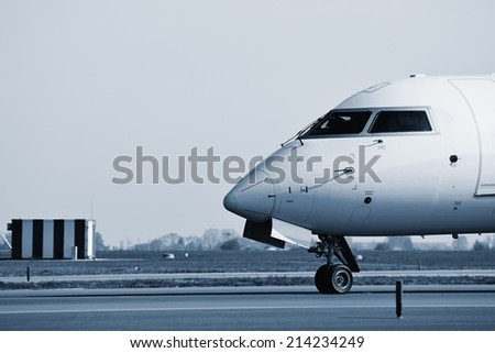 Airplane is taxiing to take off - blue toned  - stock photo