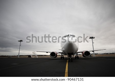 Airplane is waiting on a runway and dramatic clouds - stock photo