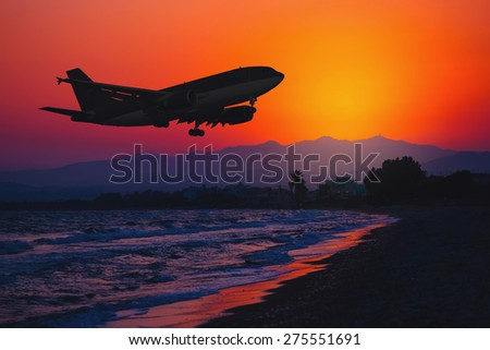 Airplane landing at sunset. Sea and Mountain background. Silhouette of a big aircraft, airline. - stock photo