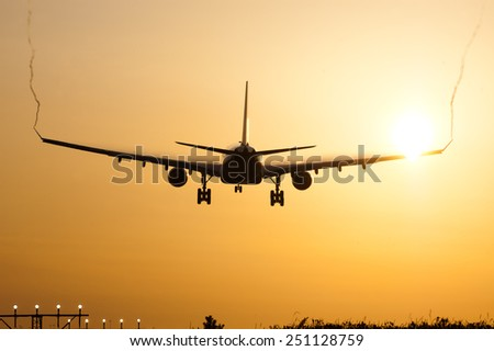 Airplane landing by sunrise - stock photo