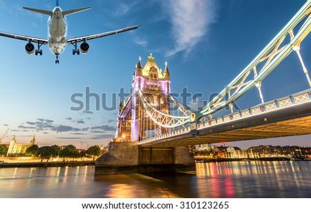 Airplane landing in London with Tower Bridge landmark. - stock photo