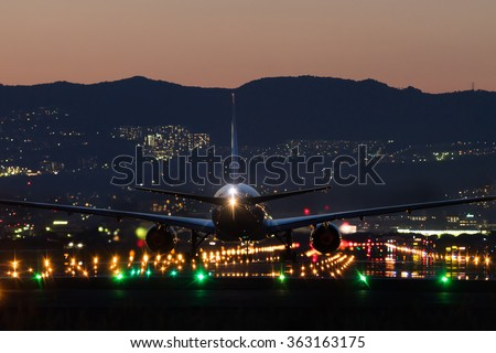 Airplane landing to the airport in sunset. - stock photo