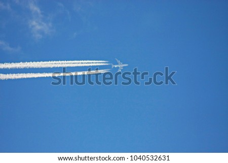 Airplane leaves chemical traces in the blue sky
