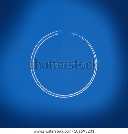 Airplane making circle trace against clear blue sky - stock photo