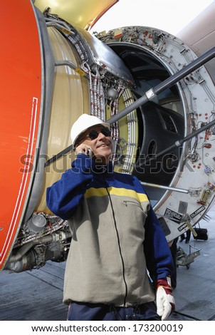 airplane mechanic talking in phone with giant open jet engine, turbine in background - stock photo