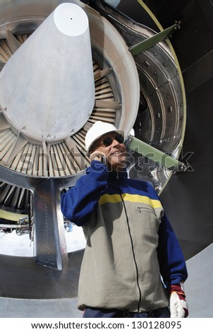 airplane mechanic talking in phone with jumbo jet-engine in background - stock photo