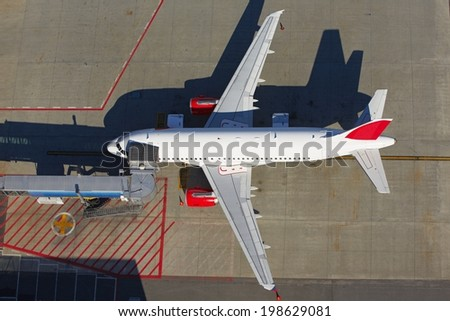 Airplane near terminal building of the airport - stock photo