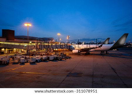Airplane near the terminal in an airport at the dusk, Changi international airport - stock photo