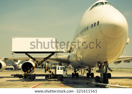 Airplane near the terminal in an airport cockpit, vintage color style - stock photo