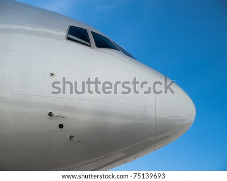 Airplane nose details against clear blue sky - stock photo