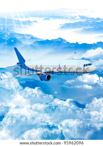 Airplane on a blue and cloudy sky. Airplane over the mountains - stock photo
