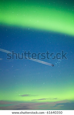 Airplane on moon lit night sky with intense Aurora borealis (northern lights) display and lots of stars. - stock photo