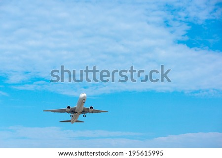 Airplane on the blue cloudy sky background. Room for text