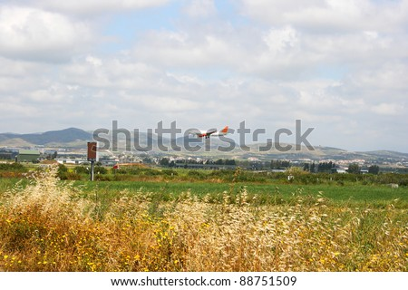 Airplane over fields in Cyprus. - stock photo