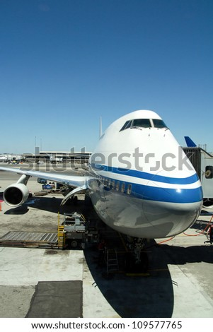 Airplane parked at airport terminal with aerobridge connected - stock photo