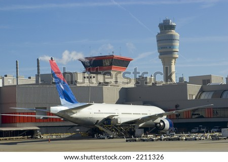Airplane parked at the terminal with the control tower in the background - stock photo