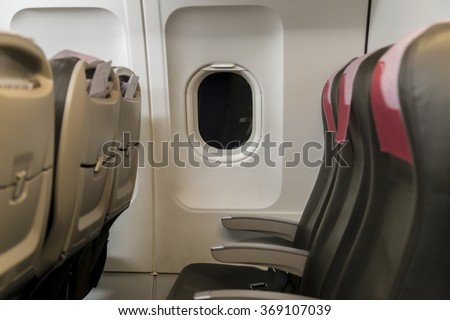 Airplane passenger seats during night flight with low light conditions - stock photo