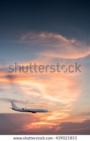Airplane plane in the sky at sunset sky - stock photo