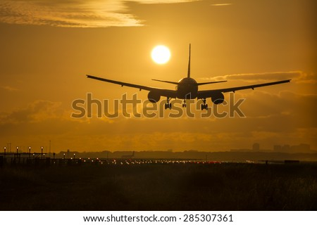 Airplane preparing for landing during sunrise.