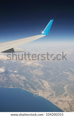 Airplane's wing under mountains and sea - stock photo