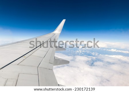 Airplane's wing with blue sky and white clouds below. - stock photo