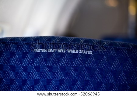 Airplane seat with seat belt placard inside an aircraft - stock photo