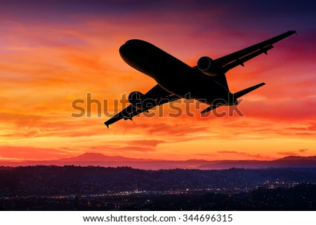 Airplane silhouette in the sky at sunset - stock photo