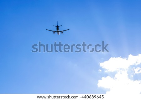 Airplane silhouette on the background of clear blue sky and sunrays. Copy space and background photo. - stock photo