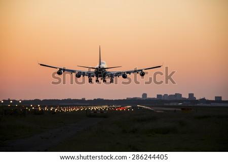 Airplane started landing couple minutes before sunrise. - stock photo