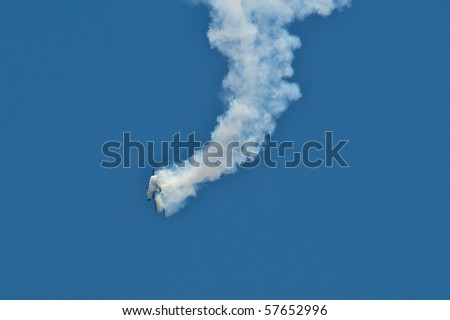 Airplane  surrounded by smoke and falling from the sky during an air show stunt. - stock photo