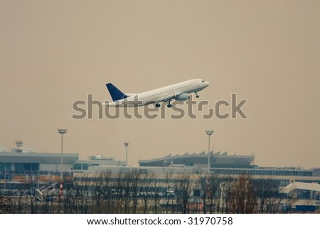 Airplane take off over an airport in twilight - stock photo