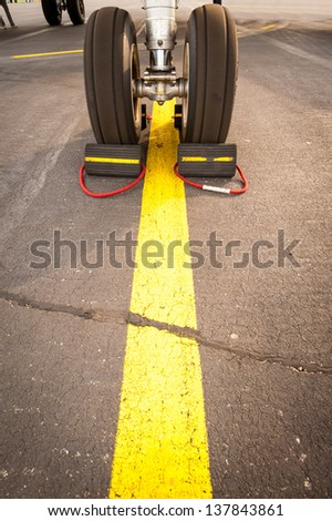 Airplane tires on yellow line, abstract transportation - stock photo