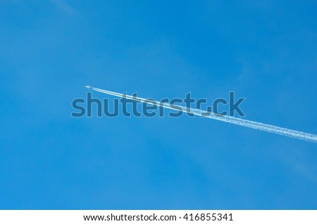 airplane trail across the blue sky - stock photo