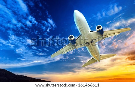 Airplane transportation. Jet air plane flies in blue sky - stock photo