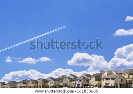 Airplane vapor trails over houses - stock photo