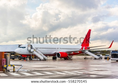 Airplane waiting for passengers at airport. Jet plane with open doors and boarding ladders ready to load passengers. Travel and transportation concepts