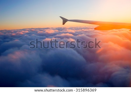 Airplane Wing in Flight from window, sunset sky  - stock photo