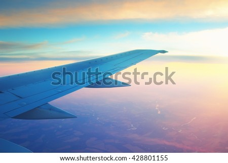 Airplane wing in the sky at sunset. - stock photo