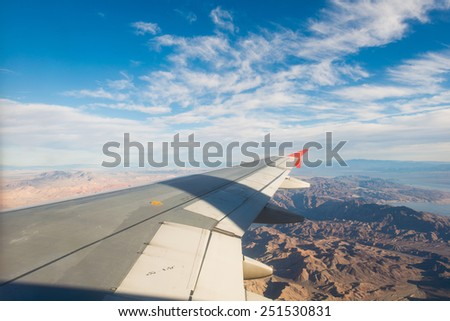 Airplane wing out of window - stock photo