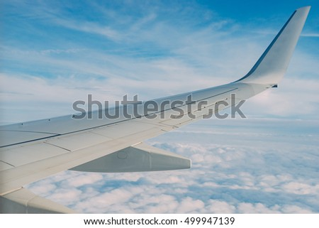 Airplane wing view out of the illuminator window on the cloudy sky background. Travel inspiration. Holiday vacation background. Business concept.