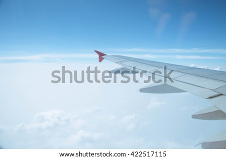 airplane wing.Wing of an airplane flying above the clouds.view sky from the window of the plane, using airtransport to travel. - stock photo