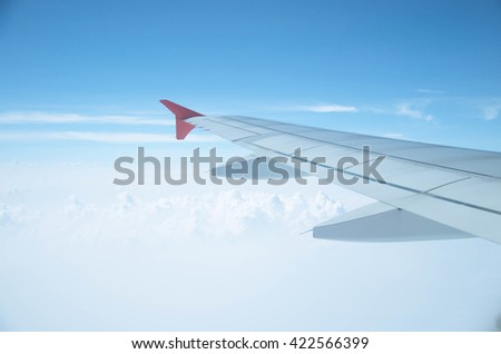 airplane wing.Wing of an airplane flying above the clouds.view sky from the window of the plane, using airtransport to travel.
