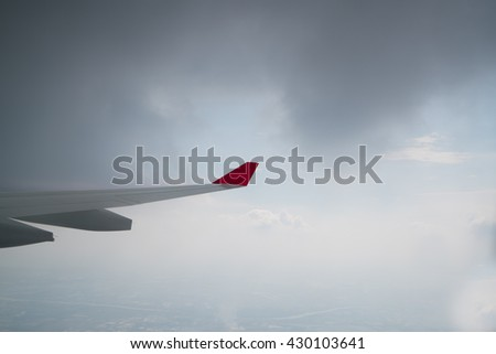 Airplane wing. Wing of an airplane flying in the dark clouds. View sky from the window of airplane, the sky's overcast. - stock photo