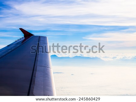 Airplane wing with Clouds, view from above. - stock photo