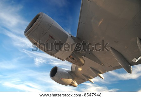 Airplane Wing with turbines against blue sky