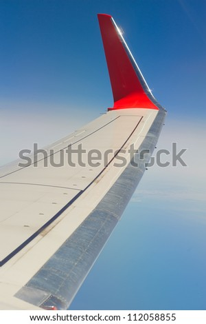 airplane wings in the blue clouds - stock photo