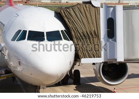 airplane with bridge attached - stock photo
