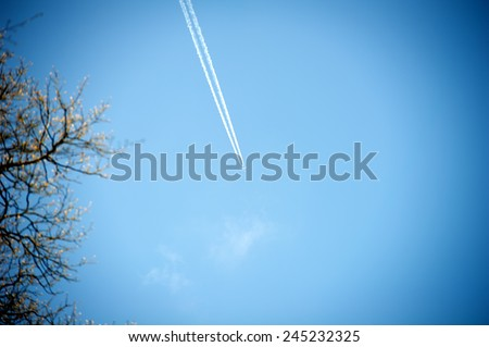 Airplane with contrail high in the sky - stock photo