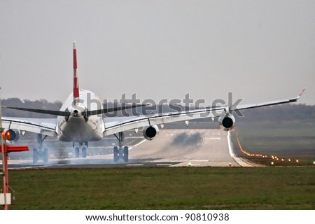 Airplane with four engines landing on runway back view - touchdown with tire smoke - stock photo